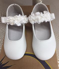 d71b8e44806b6e L AMOUR Toddler Girl s White dressy Mary Jane shoes that have White satin  flowers on the strap.