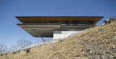 O cliente escolheu o cume de uma montanha em declive para implantar o projeto com a melhor vista possível. Um projeto do Kidosaki Architects Studio.