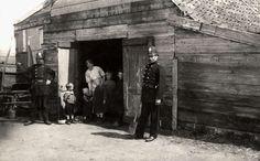 Krotten, achterbuurten, sanering: Dit gezin van een vrouw en vijf kinderen bewoont een varkenskot waarin ook nog twee varkens en vele ratten hun verblijf houden. Den Haag, Nederland, 1920.