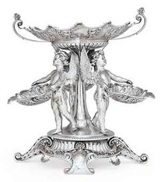 VICTORIAN SILVER FIGURAL CENTERPIECE MARK OF WILLIAM HUTTON & SONS, LONDON, 1898 On shaped circular stand, with four scrolling feet, the center set with three figures of winged putti each holding a leaf-shaped dish, supporting a scalloped circular center dish with flying scroll handles, marked on stand and putti, dishes and two nuts