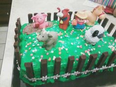 Farm Animal birthday cake. 2 sheet cakes with green frosting, milk chocolate icing for mud hole, fisher price farm animals, flower sprinkles, kit kat bars for fence, & I got the flower ribbon at the craft store