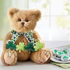 Back in the old country, St Patrick's day is a totally different celebration. Shamrocks abound on both sides of the pond, and this darling bear holds a banner of cutouts and brings a gift of choco . Spring Flower Arrangements, Spring Flowers, 800 Flowers, Chocolate Wrapping, Banner Images, St Pats, Good Cheer, Green Gifts, St Patricks Day