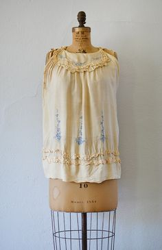 1920s cream colored raw silk top with charming blue floral embroidery. Vintage 20s top features  scalloped collar and trimmed in ruffles along the bottom and arm holes. Has snaps at the shoulders for closure.