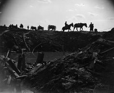 Battle of Ypres. Remains of the Menin Road near Gheluvelt Limbers held up by impassable road and shells being taken forward by pack mules. A crater, mud and wreck of battle in foreground. 29 September 1918. 29th Division.