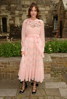 Alexa Chung in a Gucci Fall Winter 2016 dress with silk flower detail and lace-up boots.
