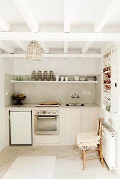 Tiny yet functional kitchen, with open shelves, mini fridge, and exposed beams.