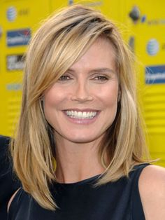 Heidi Klum sporting a long blonde bob with a large side swept bang. // Heidi Klum portant un carré long et blond, avec une longue frange sur le côté.