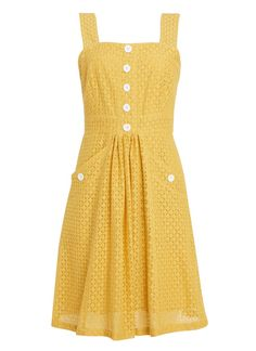 The Vida sun dress is available in yellow or classic navy, featuring a cutwork pattern, pockets and contrast buttons for sweet summer holiday style.