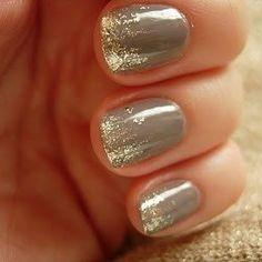 Bonitas uñas en color gris con brillos dorados adornando las puntas.