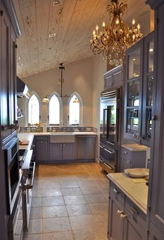Designed to look like an old French bakery, this kitchen has purple-blue painted cabinets, blue and white tile, glass Urban Archeology display shelves backed by beveled mirrors, stainless Wolf stove and hood, original lancet windows and antique crystal chandelier,  white farm sink, white statuary marble countertops, and vaulted peck cypress ceiling.