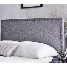 Add simple elegance to your bedroom with this inviting padded gray fabric headboard with stylish nailhead trim around its rectangular perimeter.