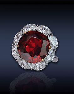 Ruby & Diamond Solitaire, Featuring: 10.01 Ct Cushion Cut Ruby, Surrounded by 3.74 Ct Oval Cut Diamonds (8 Stones), Mounted in Platinum and 18K Yellow Gold.