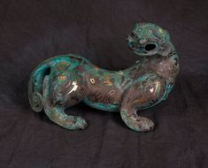 A rare gold and silver inlaid-bronze figure of a panther. Warring States Period…