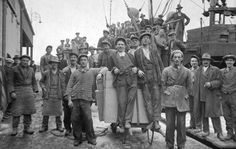 A group of dockers pause to pose for the camera as a ship is unloaded at Limerick Docks,c.1925.