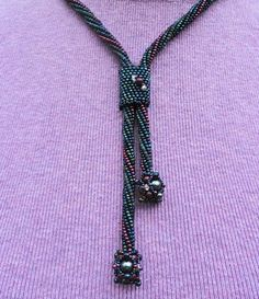 this beautiful lariat necklace is made using tons and tons of seed beads which are then sewn together one by one. There are 3 different colors in a