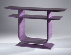 A playful take on a Émile-Jacques Ruhlmann console, in purple koto with polished aluminum rods punctuating the end of each tabletop surface and banding the bezel base.