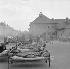 THE LIBERATION OF BERGEN-BELSEN CONCENTRATION CAMP, APRIL 1945. Sick patients lie in beds on the Parade Ground at Camp No 2, Hohne Military Barracks, until space can be found for them indoors.
