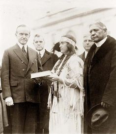 Miss Ruth Muskrat, a Cherokee Indian, presents Mr. Coolidge with a copy of The Red Man in the United States, a survey of the present day American Indian.  More about Ruth here:  http://chickamaugacherokee.org/ruthmuskrat/