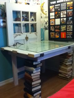 Desk that is made from an old front door, some planks of wood, and multiple old books for each of the legs.