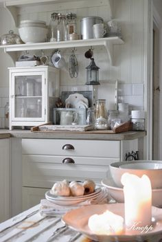 White cabinets with bin pulls, open shelving, and an eclectic collection of kitchen utensils  :)