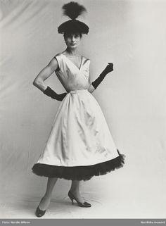 Modell i aftonklänning med svart tyllkant längst ned, svart hatt med fjäderplym…