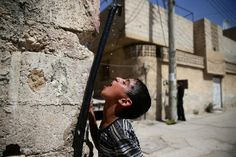 A boy drinks water from a pipe in the besieged town of Douma