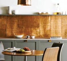 The backsplash seen in this photo from Original Style, via Ideal Home, is actually a large-format glass tile with a metallic backing.