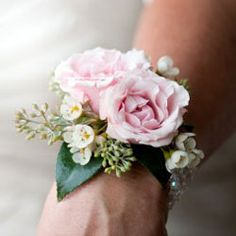 wrist corsage made with spray roses, waxflower and seeded eucalyptus