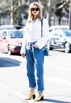 Pernille Teisbaek layers a plain white tee underneath a white cropped jacket, tucked into a pair of boyfriend jeans and a pair of metallic heels for a girly finish