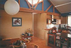 A photo of the inside of a home constructed using rammed earth walls, and timber beams in the roof.