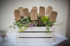Luggage tag wedding table plan with flowers and rustic box