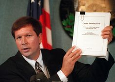 House Budget Committee Chairman Rep. John Kasich, R-Ohio, holds the Republican budget plan during a debate with Budget Director Alice Rivlin, Thursday Oct. 19, 1995 at the National Press Club in Washington. Kasich said that the Republicans have a deal to balance the budget in seven years and will not wait to balance any longer. (Photo: Doug Mills/AP)
