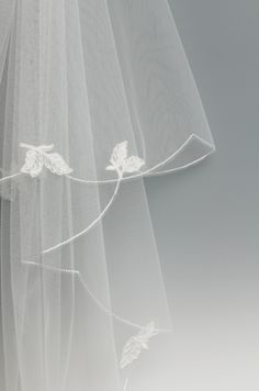 Two tier veil with an ivory embroidered scalloped edge, decorated with touches of corded lace all the way around the veil.