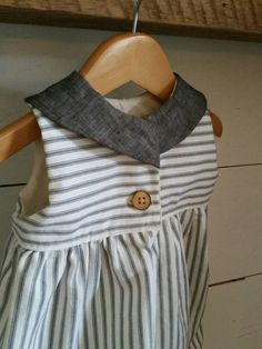 Beautiful baby/childs dress, made with a gorgeous grey ticking cotton duck cloth. This darling dress is truly a timeless piece. The back has a button closure.  Bodice is lined with a cream cotton, and top has a black linen pan collar. Fabric is medium weight, a little heavier than other fabrics in my shop.   This is one staple in her closet that will get plenty of wear from play to party!  Care: Cold water wash gentle cycle- hang dry. Iron as needed