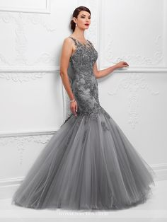 Sleeveless tulle and metallic lace mermaid gown with hand-beaded lace illusion Sabrina neckline, sweetheart dropped waist metallic lace bodice, beaded lace illusion keyhole back, voluminous gathered tulle skirt, slight sweep train. Matching shawl included. Sizes: 4 – 20 Colors: Pewter/Gray, Oyster/Silver