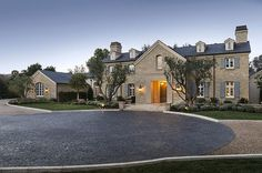Beautiful stone home is accented with gray shutters along with a circular driveway.