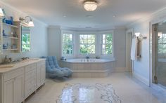 An unequalled spa-bath with intricate mosaic tile floor, spa-tub, marble-clad steam shower, and custom double vanity.