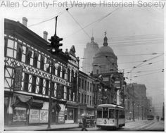 Photograph of Calhoun Street as seen from Columbia Street, Fort Wayne, Indiana, around 1935. Allen County Courthouse and Lincoln Tower building are in the background. This block was later torn down for the City-County Building. Photograph includes electric street cars. 1935