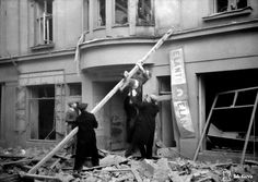 Finnish civilians rescue a woman from a bombed building during the first day of Soviet military actions taken against the Finnish capital of the Finnish-Soviet Winter War. The Winter war began with Soviet invasion of Finland on 30 Nov 1939 (3 months after the outbreak of the war in Europe), and ended with the Moscow Peace treaty on 13 Mar 1940. It would soon be followed by the Continuation War between the two nations from 25 June 1941 to 19 Sept 1944. Helsinki, Uusimaa, Finland. 30 Nov 1939.