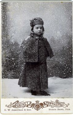 +~+~ Antique Photograph ~+~+   Young girl not looking too happy about being out in the snow, even if it's fake snow ;)   North Bend, Nebraska
