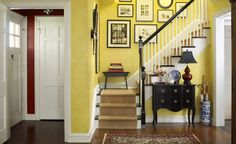 Buttery yellow walls and a perfectly arranged photo gallery highlight the stairwell in this 1937 Dutch Colonial Revival. A burgundy table lamp picks up the foyer's wall color, while a blue and white Oriental umbrella stand completes the primary color scheme. Black accents give the colorful space an air of formality. Recreate the look for your own entryway with our collection of products at Wayfair.com