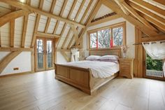 Lovely Master Bedroom set into exposed oak rafters in this stunning house in Scotland by Roderick James Architects