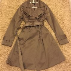 Bebe trench coat in champagne color Beautiful champagne colored 3/4 length with belt, Bebe coat. Great used condition. bebe Jackets & Coats