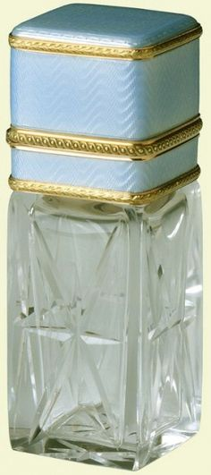 Scent bottle of rock crystal, square in section with four panels of eight-pointed stars, red gold collar and hinged lid with pale translucent blue guilloché enamel and palm leaf bands. Mark of Henrik Wigström; gold mark of 56 zolotniks (1896-1908)