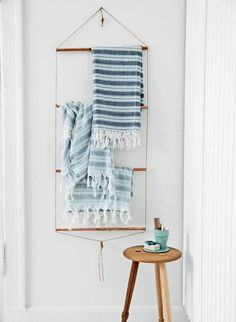 Minimalist Scandinavian copper and cord towel hanger DIY tutorial. It's made with four copper pipes, strong cord and large wood beads. The cord is drawn criss-crossed through the pipes and the wood beads are used at the top and bottom of the holder. (Original instructions in Danish.) The towels in the photo are from Fabric Copenhagen.