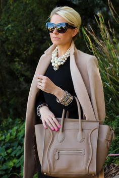 Camel coat, little black dress, camel leather tote, oversized black cat eye sunglasses, and oversized pearls