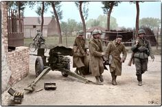 Captured French soldiers of the 158eme Regiment d'Infanterie (43eme Division d'Infanterie) carry a wounded comrade past a damaged French 25mm Hotchkiss (SAL Mle 34) anti tank gun which was positioned at crossroads in the Belgium village of Thulin. 23rd May 1940.
