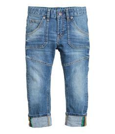 Azul denim. Vaqueros de cinco bolsillos en denim elástico y lavado con cinturilla elástica ajustable, cierre con cremallera y botón de presión y secciones