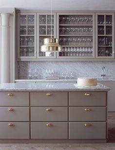 gray cabinets brass campaign hardware white carrera marble countertops by Ilse Crawford
