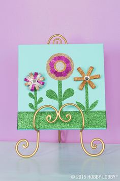 This tape masterpiece starts off with sparkly green grass and stems (tape, of course) on a canvas painted a soothing blue. And it's finished off with whimsical tape flowers.